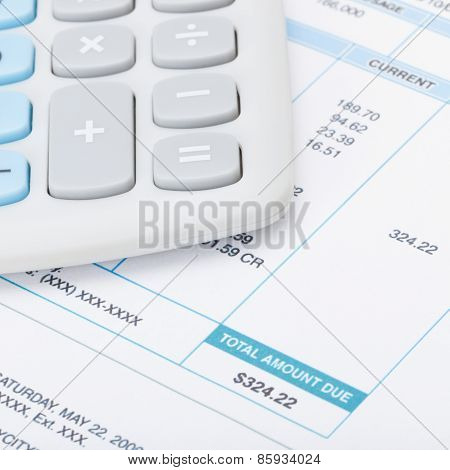 Neat Calculator With Utility Bill Under It - Studio Shot