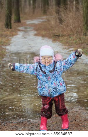 Two years old girl exploring icy puddle