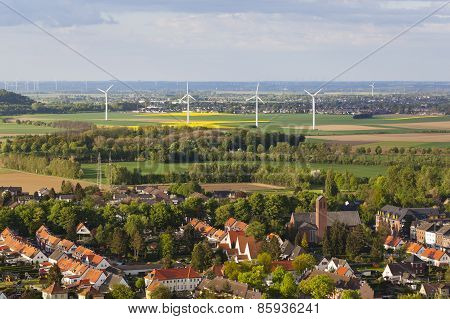 Village And Wind Turbines In Flat Landscape