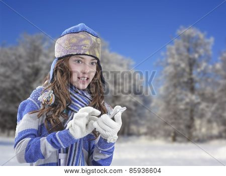 Girl in winter clothing with smartphone