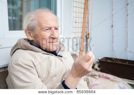 Old Man Enjoying A Cigarette