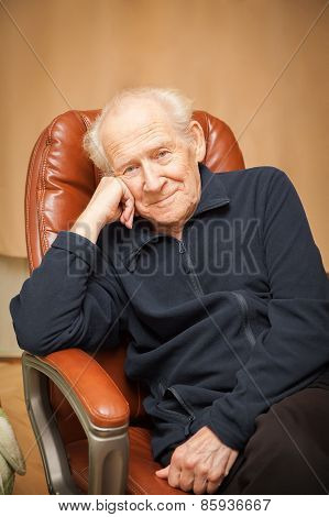 Portrait Of A Smiling Old Man In A Chair