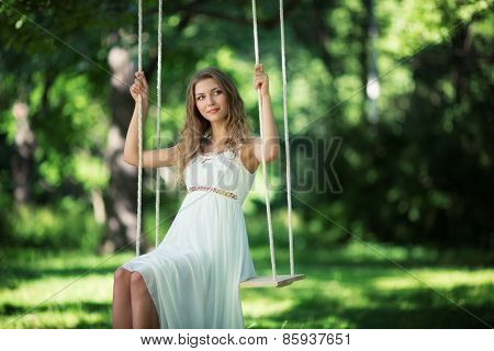 Young attractive girl on a swing