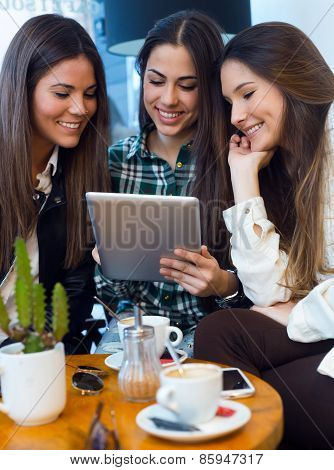 Three Young Woman Using Digital Tablet At Cafe Shop.