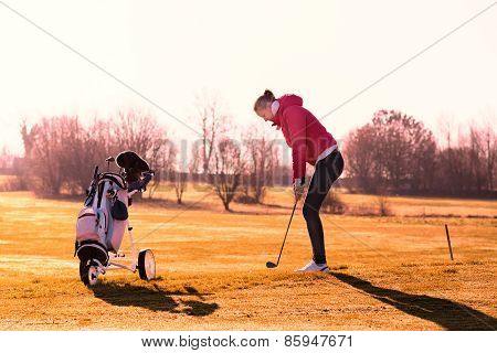 Woman Golfer Playing A Round In Evening Sunlight