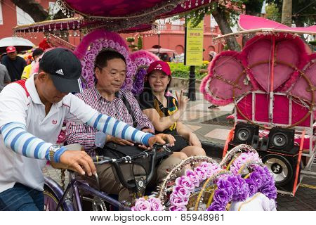 MALACCA, MALAYSIA - CIRCA JANUARY, 2015: Tourists traveling in a rickshaw at the Dutch Square in Malacca. Malacca was included in the list of UNESCO World Heritage Sites in 2008.