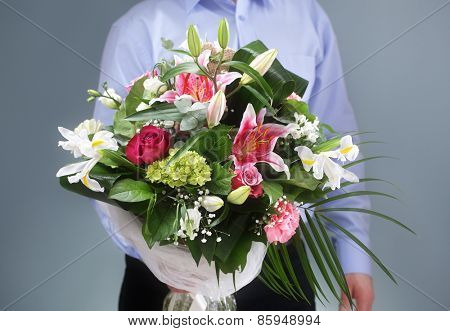 Businessman holding and giving a bouquet of flowers