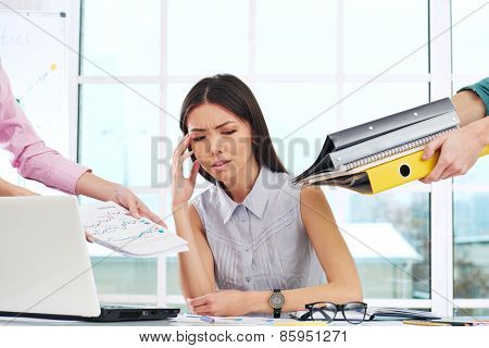 Tired overworked young businesswoman with folders