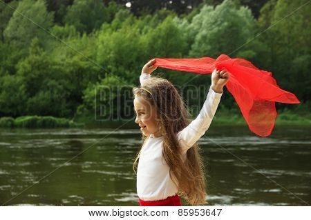 Portrait of little cute girl dance with red Scarf by the river