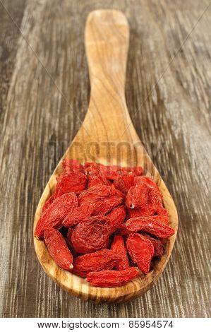 Spoon of goji berries over wood