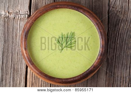 Tasty green cream vegetarian soup meal in wooden bowl on vintage table