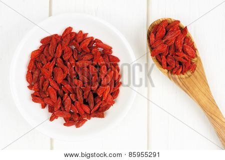 Bowl of goji berries on white wood with spoon