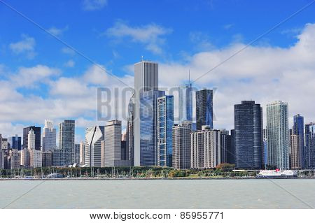 Chicago city urban skyline with skyscrapers over Lake Michigan with cloudy blue sky.