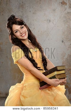 Young  woman dressed in princess costume holding books in old room