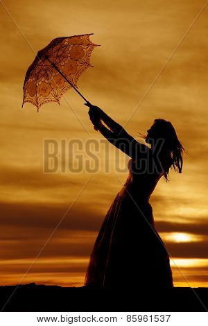 Silhouette Of A Woman In A Dress With An Umbrella Blowing Above Her