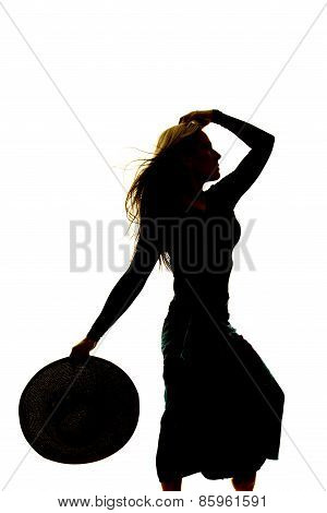 Silhouette Of A Woman In A Skirt Holding Hat Down
