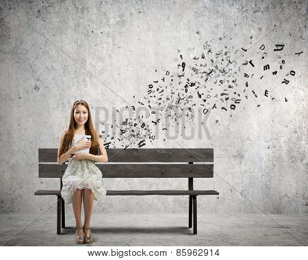 Young pretty asian woman sitting on bench and reading book