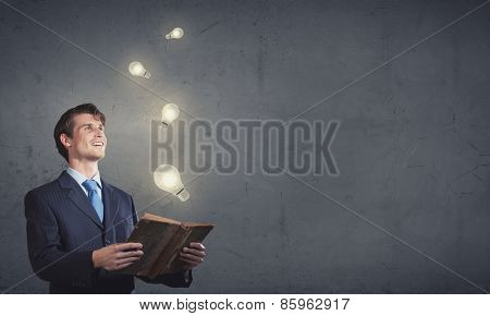 Handsome young man in suit with book in hands