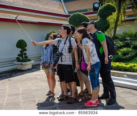 Students visiting a temple in Bangkok take a selfie