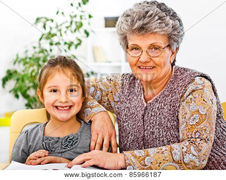 Grandmother and daughter finish child homework at domestic room smiling