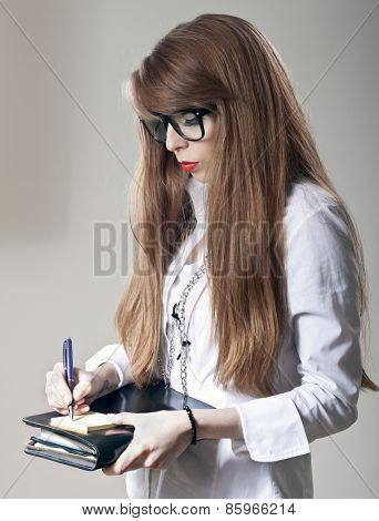 Young business woman with notebook writing