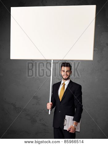 Young businessman holding a blank whiteboard