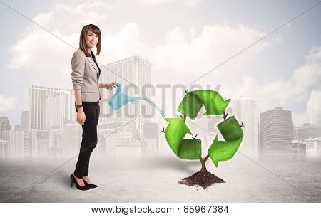 Business woman watering green recycle sign tree on city background concept