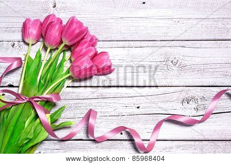 Bouquet of spring pink tulips with ribbon on wooden background