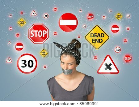 Young woman with taped mouth and traffic signals around her head