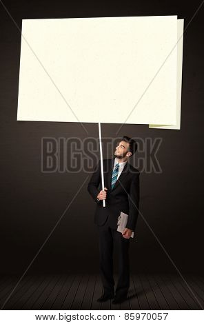 Young businessman holding a big, white post-it paper