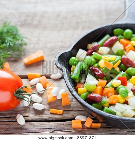 Mixed Vegetable Meal In Old Frying Pan Closeup And Ingredients On Wooden Rustic Table.