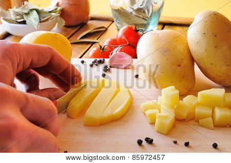 Chef Cutting Potatoes On A Cutting Board In The Kitchen