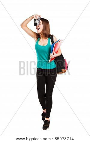 Beautiful young teenager girl student posing with notebooks and camera