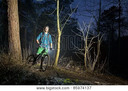 Young, handsome mountain biker smiling and posing on an off road trail at dusk, standing on his bike, wearing a helmet, shorts, as well as the proper protection: gloves, knee protectors,