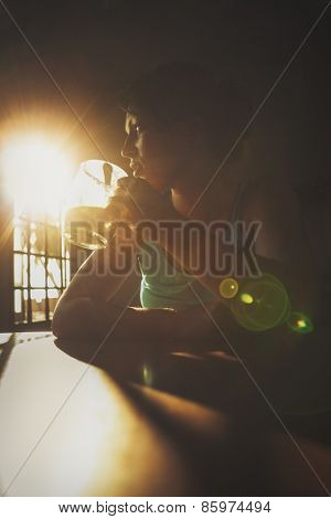Woman having a cup of drink in a room with morning sun shining through the window