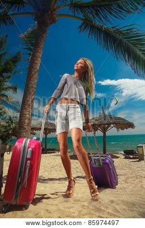 Pretty girl with a suitcases and on a resort