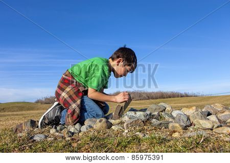 Boy Lifts Rock In Field.