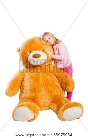 Little cute girl with big smile holding huge Teddy bear.