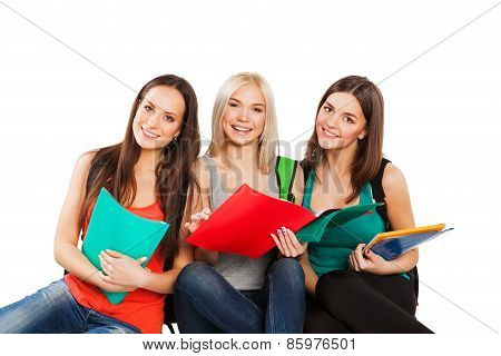 Three happy students standing together with fun, while smiling and looking at camera isolated on whi