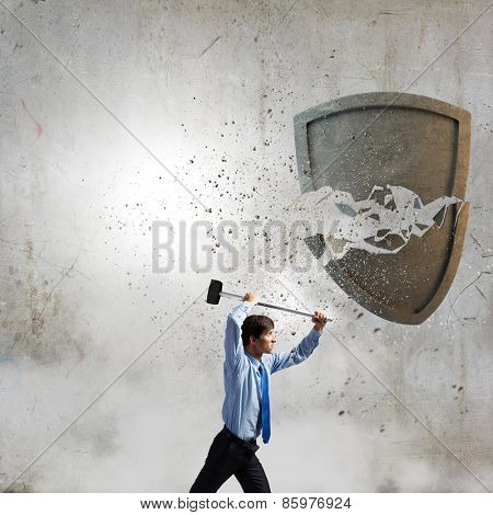 Young businessman crashing stone shield with hammer