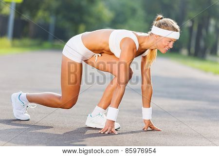 Bottom view of young sport woman in start pose