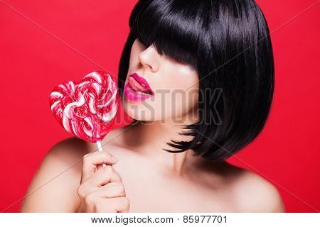 Closeup photo of a beautiful sexy pink lips with lollipop on red