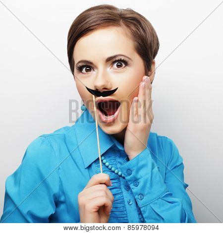 Girl wearing fake mustaches. Ready for party.