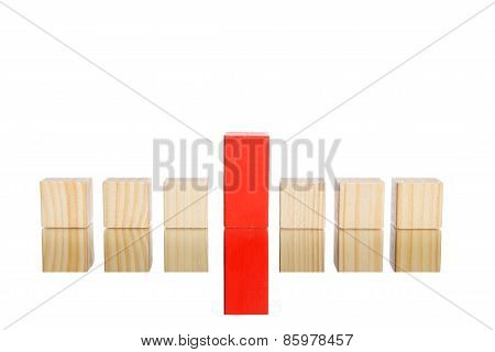 wooden blocks standing in line with big red one in the centre