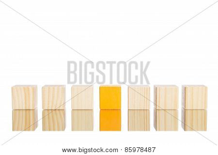 wooden blocks standing in line with orange one in the centre