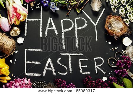 Easter greetings on a blackboard with eggs, flowers and nest