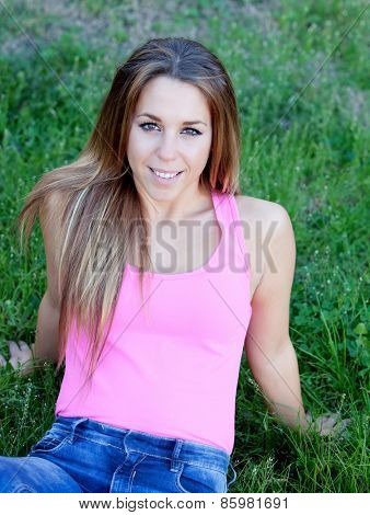 Cool pretty woman with pink t-shirt sitting on the grass