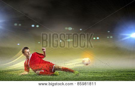 Young football player on stadium kicking ball