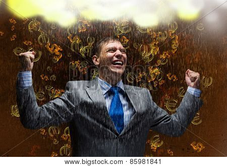 Young joyful businessman with hands up celebrating success