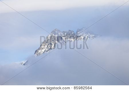 Mountain peak in the cloud-based sky